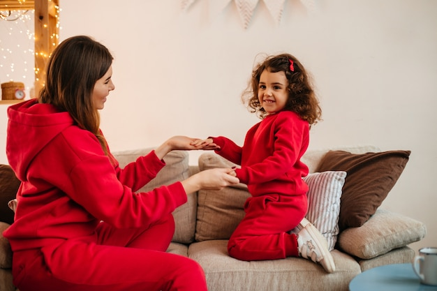 Curly preteen kid holding hands with mother. indoor shot of young woman playing with daughter at home.