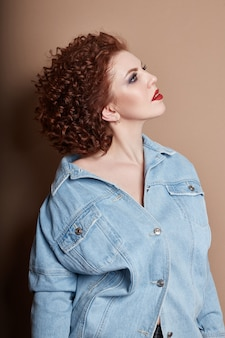 Curly red-haired adult woman in a blue denim shirt