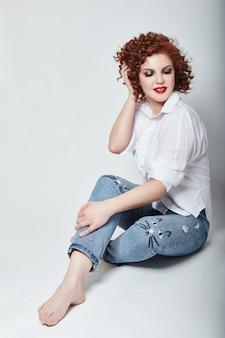 明るい背景のスタジオに座ってポーズをとる白いシャツとブルージーンズの巻き毛の赤毛の大人のセクシーな女性。ロシア、スヴェルドロフスク、2018年3月13日