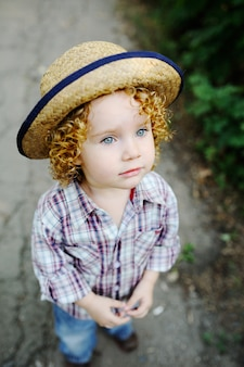 Curly redhead child in a straw hat