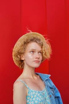 濃い赤の背景の上に立っている麦わら帽子青いサンドレスとデニムジャケットの巻き毛の赤毛の女性