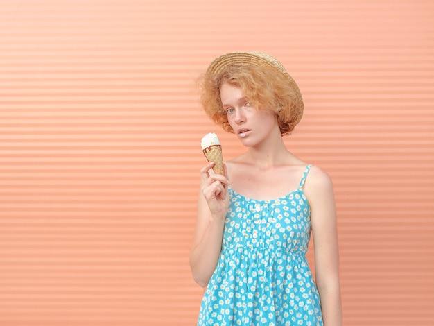 超高層ビルの屋根のスカイルーフでアイスクリームを食べる麦わら帽子青いサンドレスの巻き毛の赤毛の女性
