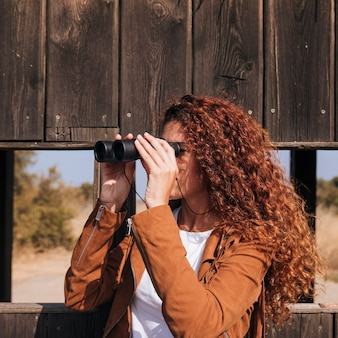 Curly redhead woman watching through binoculars