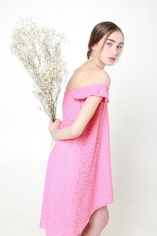 곱슬곱슬한 로맨틱한 모습, 아름다운 눈. 손에 흰 야생화입니다. 소녀 흰색 빛 드레스와 곱슬 머리, 흰색 배경에 꽃을 가진 여자의 초상화, 순결과 순수