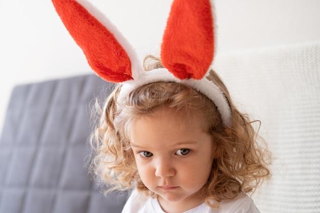 Курчавая грустная маленькая милая кавказская девушка в ушах зайчика, сидя на софе. пасхальный.