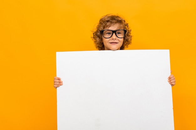 Curly schoolboy in glasses for vision on a background of an orange wall holds a large blank form in his hands