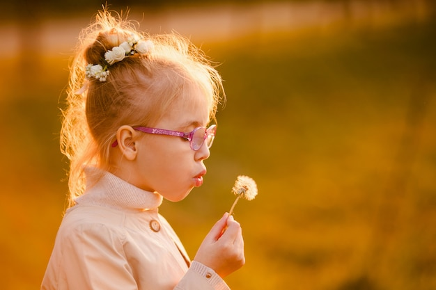 Curly schoolgirl in the glasses and light coat blowing at dandelion in the autumn park on the sunset