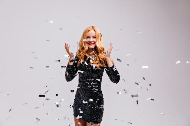 파티를 즐기는 검은 드레스에 곱슬 관능적 인 여자. 색종이와 흰 벽에 춤 웅장 한 머리 국방과 소녀.