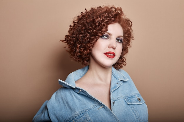 Curly sexy red-haired adult woman in a blue denim