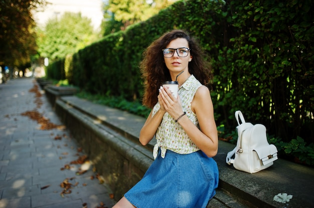Curly stylish girl wear on blue jeans skirt, blouse and glasses posed at street of city with cup of coffee.