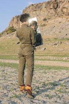Кудрявая стильная модель в коричневом комбинезоне смотрит в зеркало с растерянным выражением лица