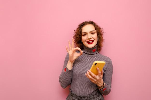 그녀의 얼굴에 스마트 폰과 미소를 들고 곱슬 십 대 소녀는 카메라에 보이는 확인 제스처를 보여줍니다