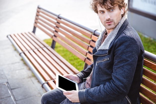 Curly thoughtful pensive attractive guy resting on wooden bench in the park with blank screen tablet