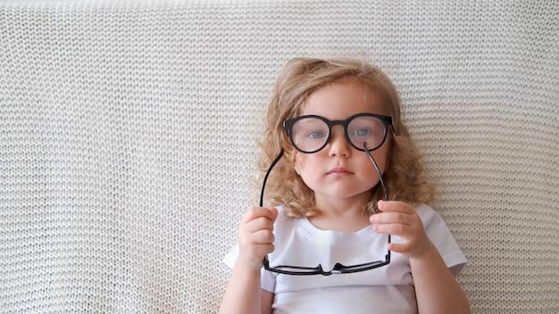 巻き毛の幼児のスマートな白人の女の子はソファに座って別の眼鏡をかけます。