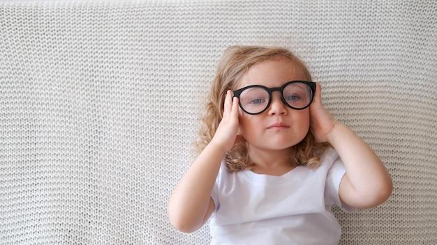 巻き毛の幼児のスマートな白人の女の子はソファに座って眼鏡をかけます。
