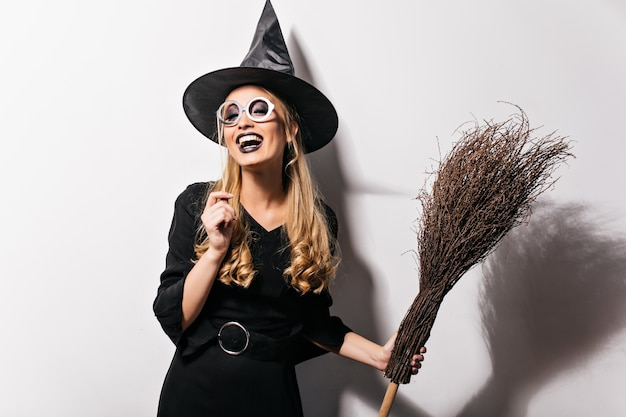 Кудрявая ведьма в очках, выражающая счастье в хэллоуин. крытая фотография смеющейся красивой девушки в костюме волшебника, держащей веник.