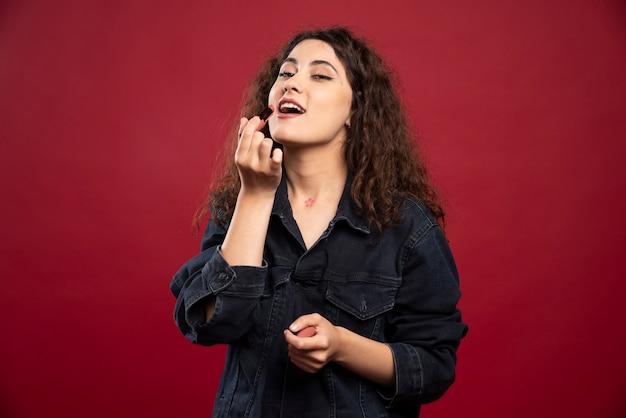 립스틱을 적용하는 곱슬 여자.