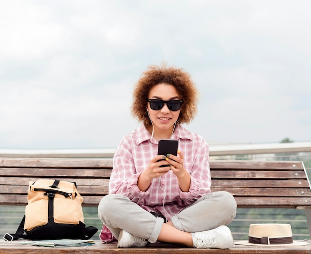 Curly woman checking her phone on a bench
