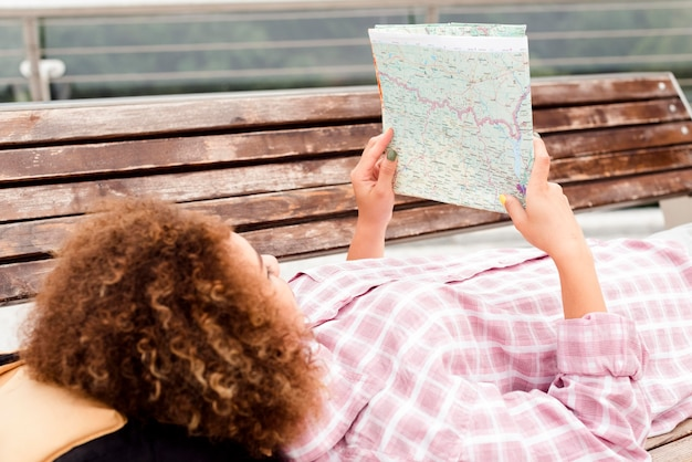 Curly woman checking a map on a bench
