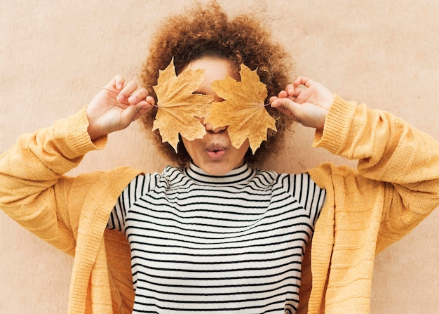 Curly woman covering her eyes with leaves