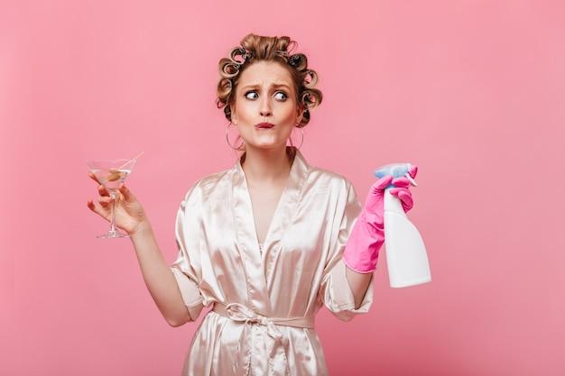 Donna riccia vestita in accappatoio in posa sulla parete rosa con bicchiere da martini e detersivo