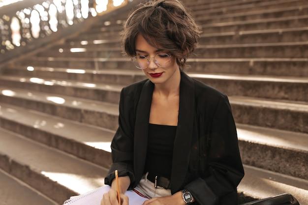 Donna riccia in occhiali e giacca nera scrivendo all'aperto. bella donna con rossetto rosso e capelli castani che si siede sulle scale.