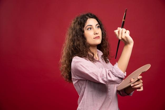 Donna riccia che tiene il pennello e la tavolozza della vernice.