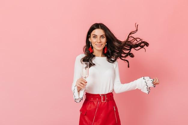 革のスカートの巻き毛の女性はピンクの背景に彼女の髪を再生します。シャンパングラスを楽しむ女性。