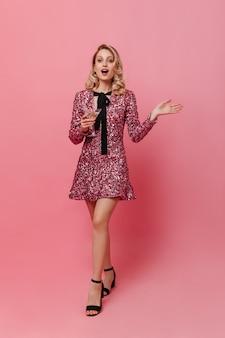 孤立した壁にマティーニグラスを保持している光沢のあるピンクのドレスの巻き毛の女性