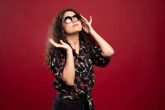 Кудрявая женщина в очках стоя.