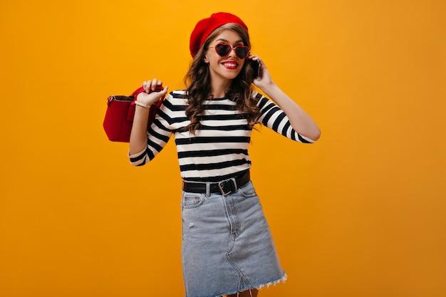 電話で話しているサングラスの巻き毛の女性。現代的な服のポーズで赤い口紅と巻き毛の魅力的な若い女性。