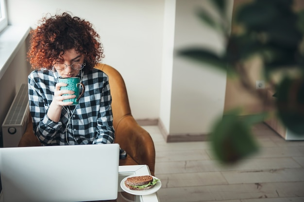 Curly woman is drinking a coffee with burger while working at a laptop from home