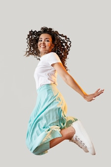 Curly woman jumping in studio