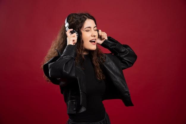 音楽を聴いて歌う巻き毛の女性。