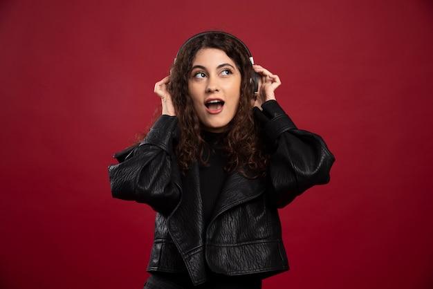 音楽を聴いている巻き毛の女性。