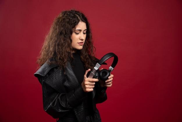 ヘッドフォンを見ている巻き毛の女性。