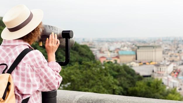 Кудрявая женщина смотрит на город через телескоп с копией пространства