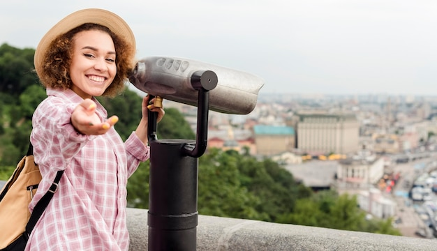 Кудрявая женщина смотрит на город в телескоп
