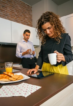 Curly woman looking electronic tablet while young man having fast coffee in home before go to work