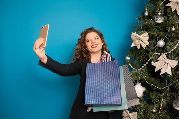 곱슬 여자는 장식 된 크리스마스 트리와 파란색 벽의 배경에 셀카를 만든다. 그녀는 선물 가방을 들고 있습니다.