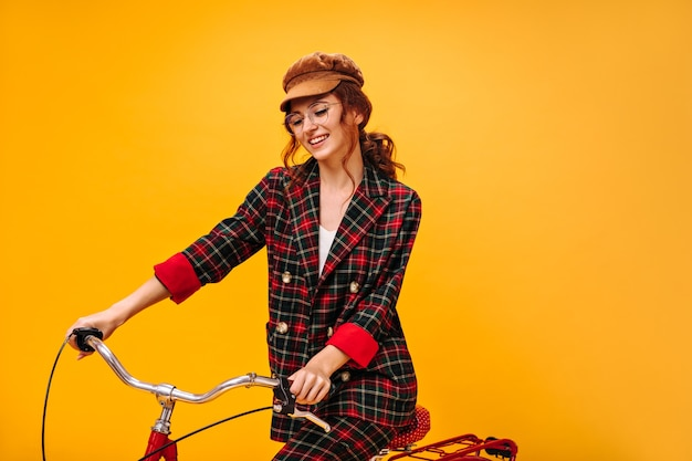 Curly woman in plaid outfit and cap riding bicycle