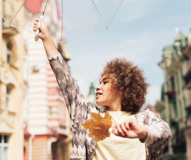 巻き毛の女性が傘でポーズ