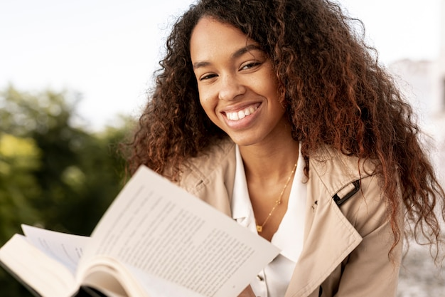 Curly woman reading a book close-up