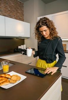 キッチンで速い朝食をとりながら電子タブレットを探して出かける準備ができている巻き毛の女性
