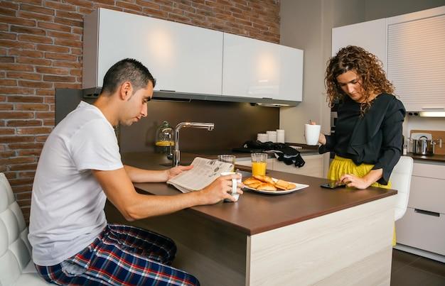 若い男が新聞を読んでいる間、家で速い朝食を食べている間、スマートフォンを探して出かける準備ができている巻き毛の女性