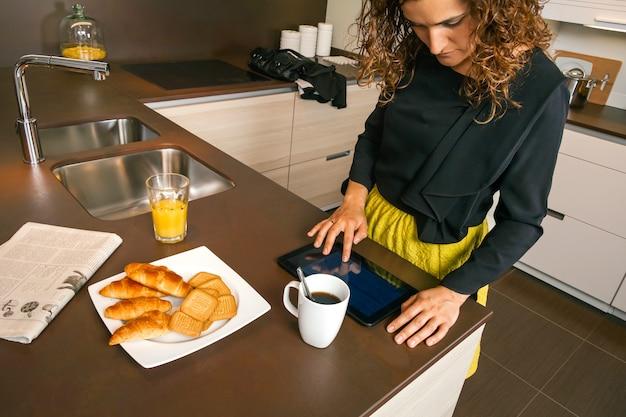 キッチンで速い朝食をとりながら電子タブレットを使用して外出する準備ができている巻き毛の女性
