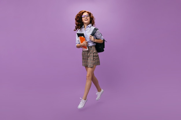 Curly woman in shirt and skirt holds backpack and notebooks Premium Photo