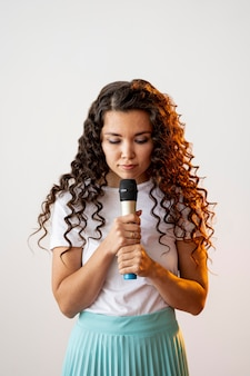 Curly woman singing at a microphone