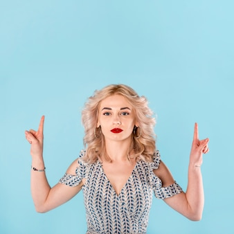 Curly woman standing and pointing fingers up