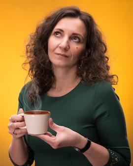 黄色の背景にお茶やコーヒーと巻き毛の女性
